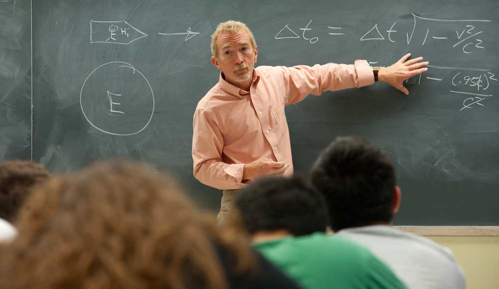 Professor pointing to blackboard in front of students