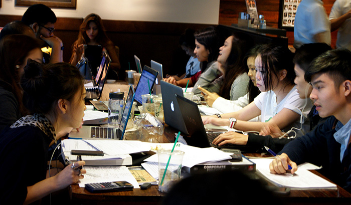 Students studying in cafe with laptops
