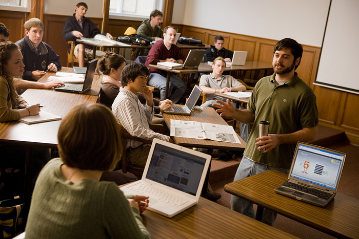 A professor talking to students in a classroom