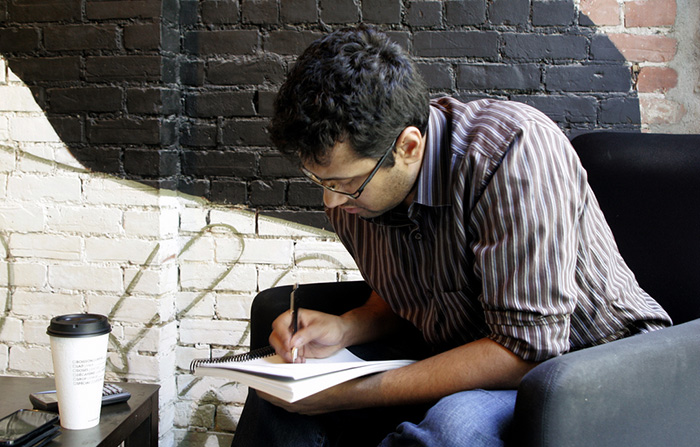 Man writing in notebook in cafe